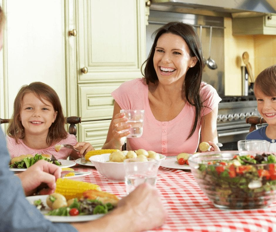 7 Reasons to Eat Family Dinner Together - family eating dinner together in the kitchen