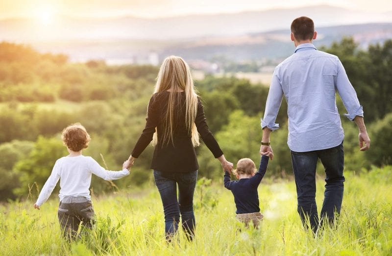 happy family walking into sunrise - passive income benefits for family
