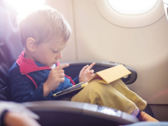 little-boy-using-tablet-on-board-of-aircraft