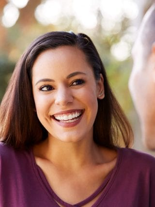 smiling hispanic couple laughing and smiling youthful younger looking skin