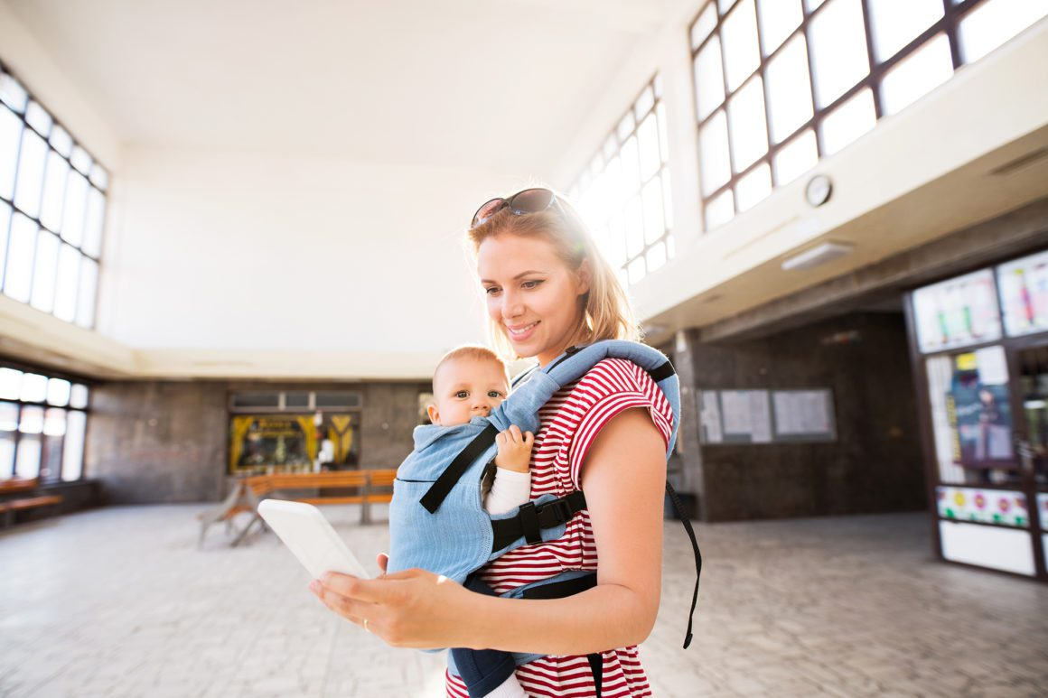 Young mother with smartphone and baby travel