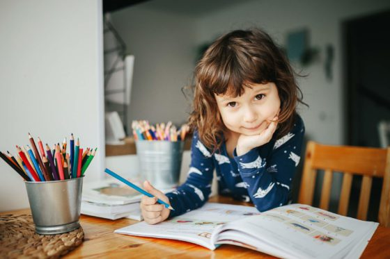 homeschool girl sitting at a table with workbooks